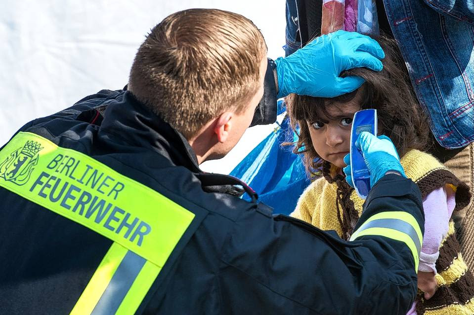 SAFE HAVEN: A German fireman takes the temperature of a young refugee girl.