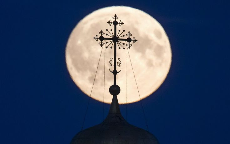 A cross atop of a local monastery is seen silhouetted against the moon in the settlement of Poschupovo in Ryazan region
