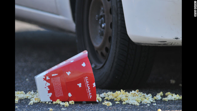 A popcorn box lies on the ground outside the Century 16 movie theatre.