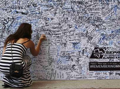 Mulher preenche painel com mensagem de apoio aos desaparecidos e seus familiares Foto: Reuters