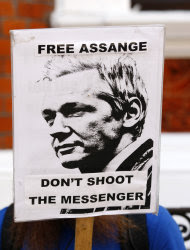 """A demonstrator protests outside the Ecuadorian embassy, London, Wednesday June 20, 2012. WikiLeaks founder Julian Assange entered the embassy Tuesday in an attempt to gain political asylum. Ecuador said Assange would """"remain at the embassy, under the protection of the Ecuadorean government"""" while authorities in the capital, Quito, considered his case. Assange was arrested in London in December 2010 at Sweden's request. Since then he has been fighting extradition to the Scandinavian country, where he is wanted for questioning over alleged sexual assaults on two women in 2010. (AP Photo/Tim Hales)"""