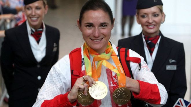 Dame Sarah Storey arrives back in the UK at Heathrow, flanked by cabin crew