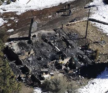 Authorities stand at a burnt out cabin near Angelus Oaks, California February 13, 2013, where police believe they engaged in a shootout with fugitive former Los Angeles police officer Christopher Dorner on Tuesday. REUTERS-Gene Blevins