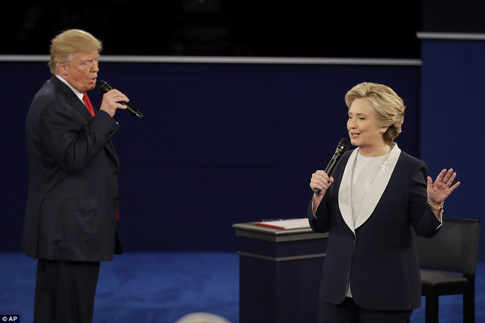 candidato republicano Donald Trump interrompe Hillary Clinton como ela responde a uma pergunta durante o segundo debate presidencial