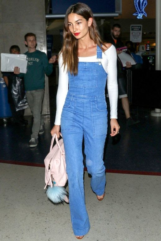 Le Fashion Blog Model Airport Style Lily Aldridge Wavy Hair Red Lips White Long Sleeve Off The Shoulder Top Wide Leg Denim Overalls Pale Pink Bag With Furry Pom Pom Charm Via Harpers Bazaar