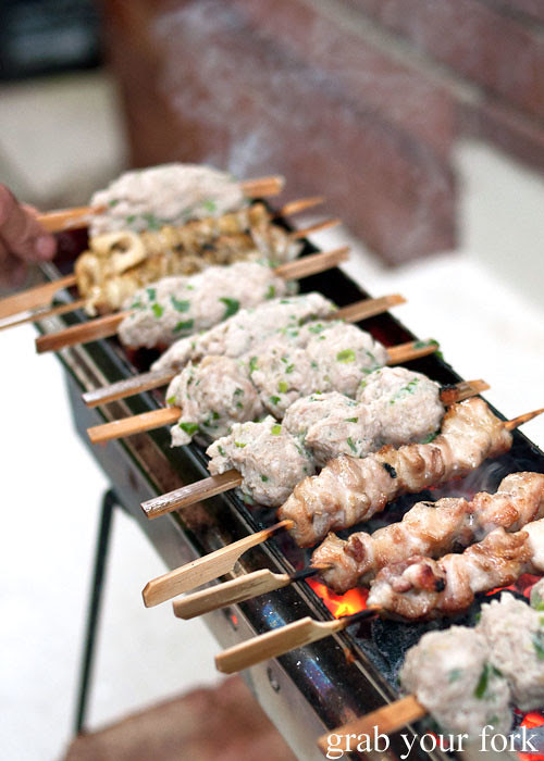 tsukune chicken meatballs on an arrosticini charcoal grill at a stomachs eleven japanese dinner