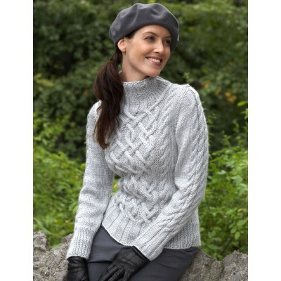 A woman wearing a cabled aran-style sweater.  There is a central cable panel, and smaller cables on each side of the panel. There are also cable twists running up the sleeves.