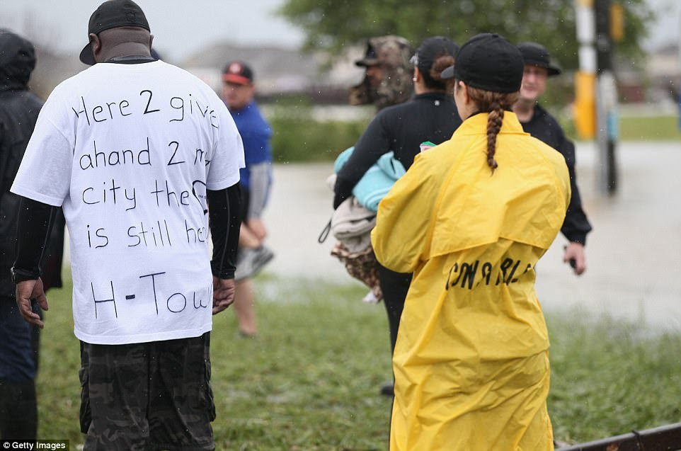 A man wearing a t-shirt with the words 'here 2 give a hand' written on the back joins volunteers in Houston on Tuesday