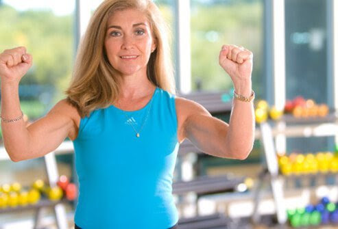 Woman demonstrating isometric exercise by tensing arm muscles.
