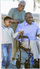 African American grandmother pusing grandfather in wheelchair grandchild walks along with them.