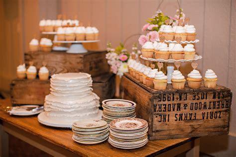 farm table holds wedding cake and cupcakes   Dream Wedding