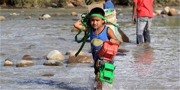 Un niño cruzando las aguas del río Táchira. Una de las imágenes más simbólicas de la crisis fronteriza.
