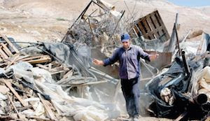 A Palestinian man inspecting the remains of his tent