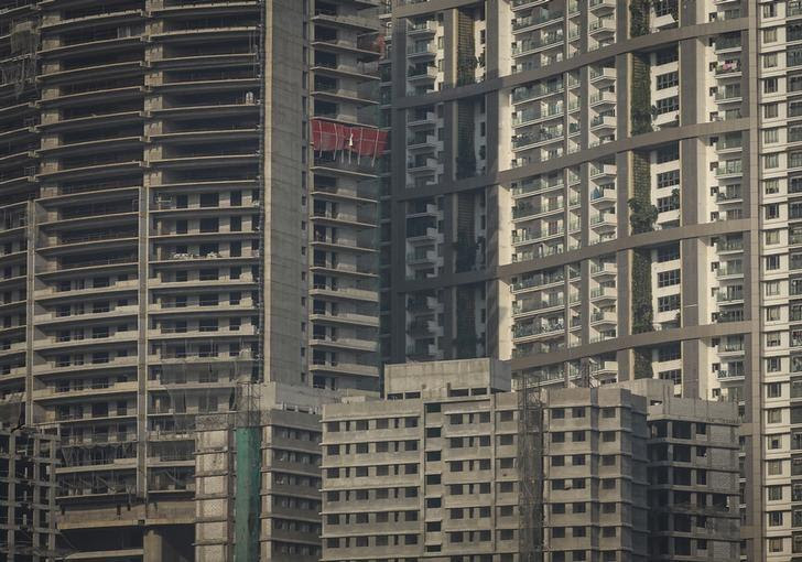 Windows of high-rise residential buildings which are under construction are seen surrounding a residential tower (R) in central Mumbai January 12, 2015. REUTERS/Danish Siddiqui/Files