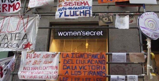 Un escaparate junto a la Puerta del Sol rodeado de carteles reivindicativos al fondo. REUTERS /Sergio Pérez
