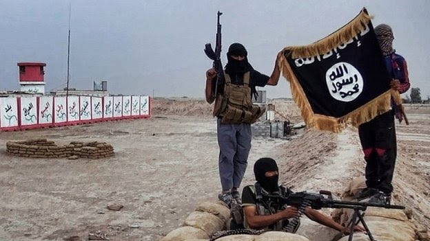 Isis fighters hold their flag aloft after taking control of an army checkpoint in the north of the country - 11 June 2014