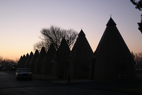 tee pee lined up with sunrise sky