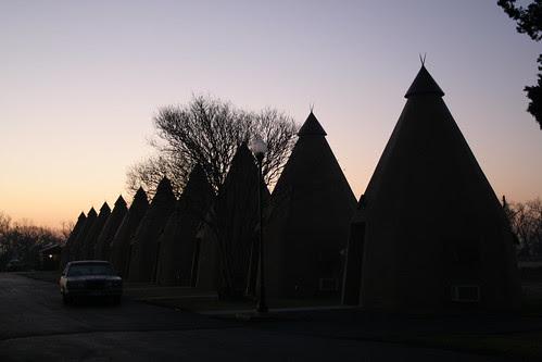 tee pee lined up with sunrise sky