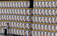 A boy walks beside a wall covered with campaign posters of Venezuela's President Hugo Chavez in Caracas, Venezuela, Tuesday, Sept. 25, 2012. Chavez held a 10-point lead over rival Henrique Capriles in a polling company's final survey ahead of the Oct. 7 election, but the report released Tuesday showed Capriles narrowing the gap. (AP Photo/Fernando Llano)