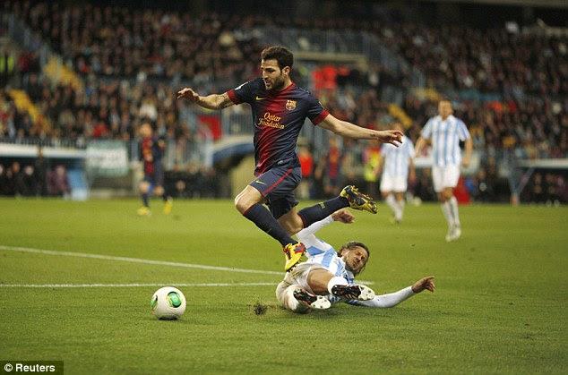 Over you go: Martin Demichelis sends Cesc Fabregas tumbling after a slide tackle