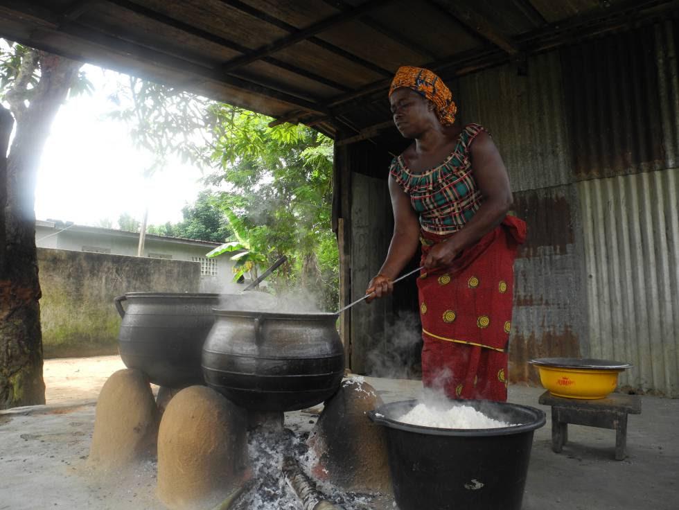 Una mujer cocina en cacerolas en el centro escolar de N'Zikro, en Costa de Marfil.