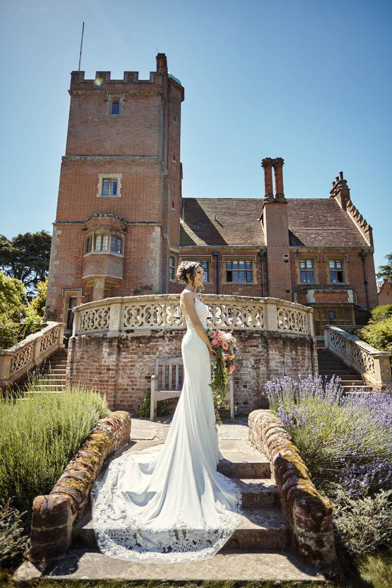 Beautiful bridal photo standing on steps in gardens of Lanwades Hall Wedding Photos - helloromancephotography.com