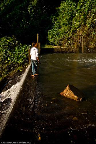 Woman crossing waters at Gangga Waterfalls
