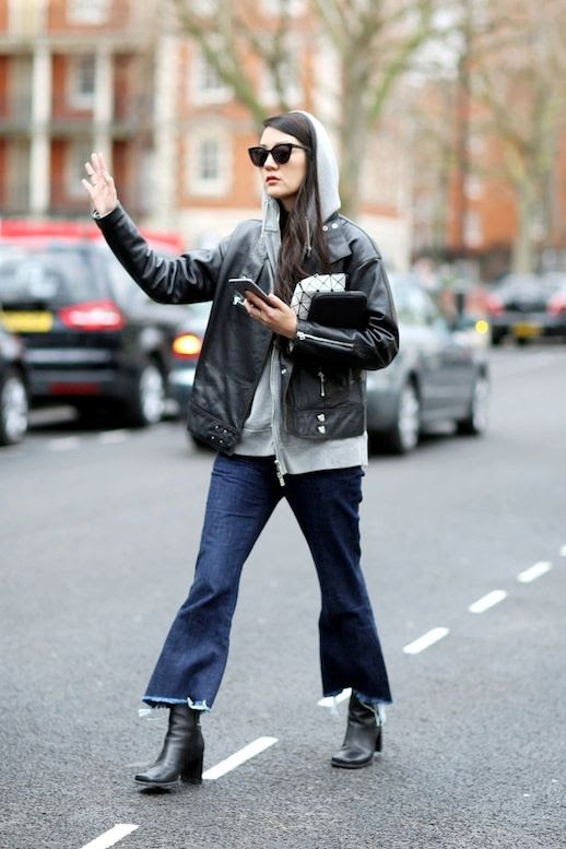 Le Fashion Blog Fall Street Style Sunglasses Oversized Black Leather Moto Jacket Grey Hooded Sweatshirt Cropped Flared Jeans With Raw Hems Ankle Boots Via Grazia