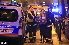 Rescue workers take a woman to safety in November 2015 after the shooting at the Bataclan music venue