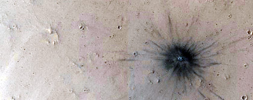 A recent impact crater on Mars. (We're pretty sure no one put out a giant cigarette here.)