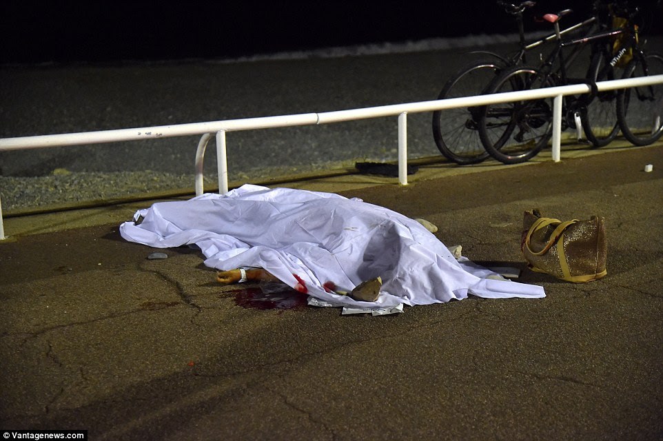 Terrible: One of the dozens of people killed by the killer lorry driver lies covered on the pavement with her handbag still next to her