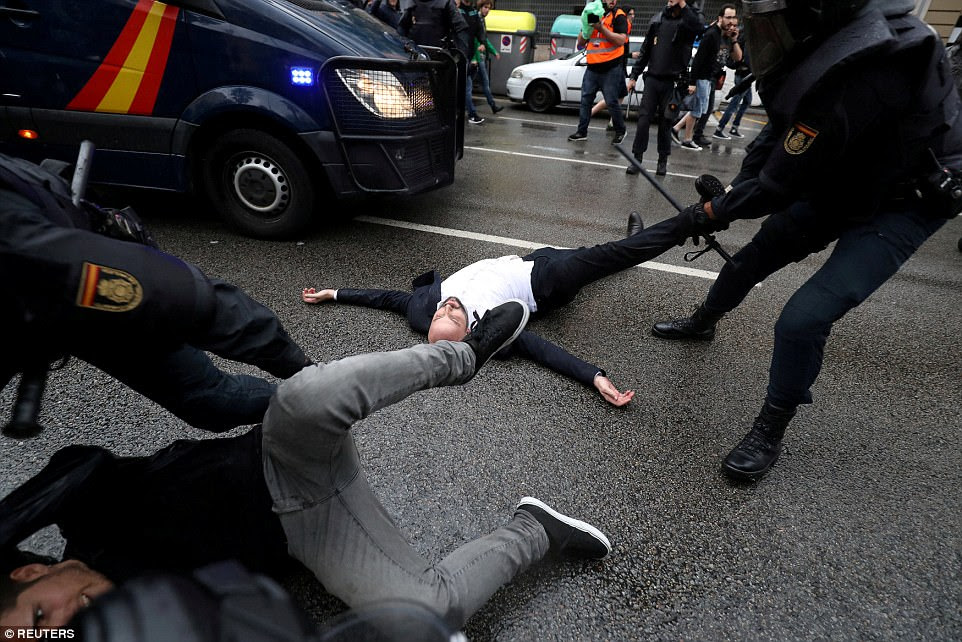 Spanish Civil Guard officers remove demonstrators outside a polling station for the banned independence referendum in Barcelona, Spain, on October 1. The region would go on to declare independence and its president would flee the country as Madrid imposed direct rule