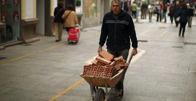 Un trabajador acarrea una carretilla con ladrillos en Ronda (Málaga). REUTERS