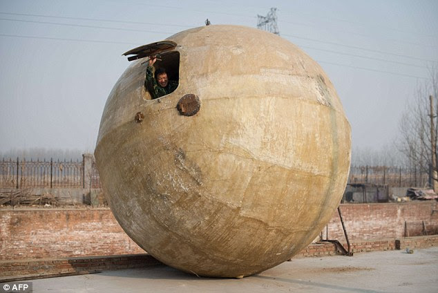 Pod almighty: Liu Qiyuan with one of his steel and fibreglass balls which, he says, can enable 14 people to escape any sort of apocalypse