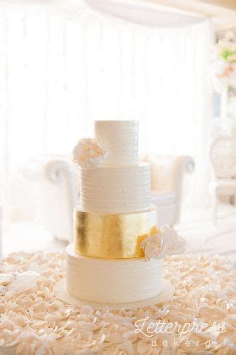 White rustic buttercream wedding cake with gold leaf tier