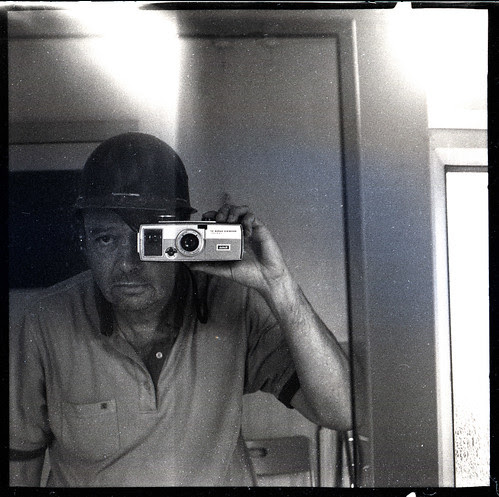 reflected self-portrait with Kodak Brownie Super 27 camera and hard hat by pho-Tony