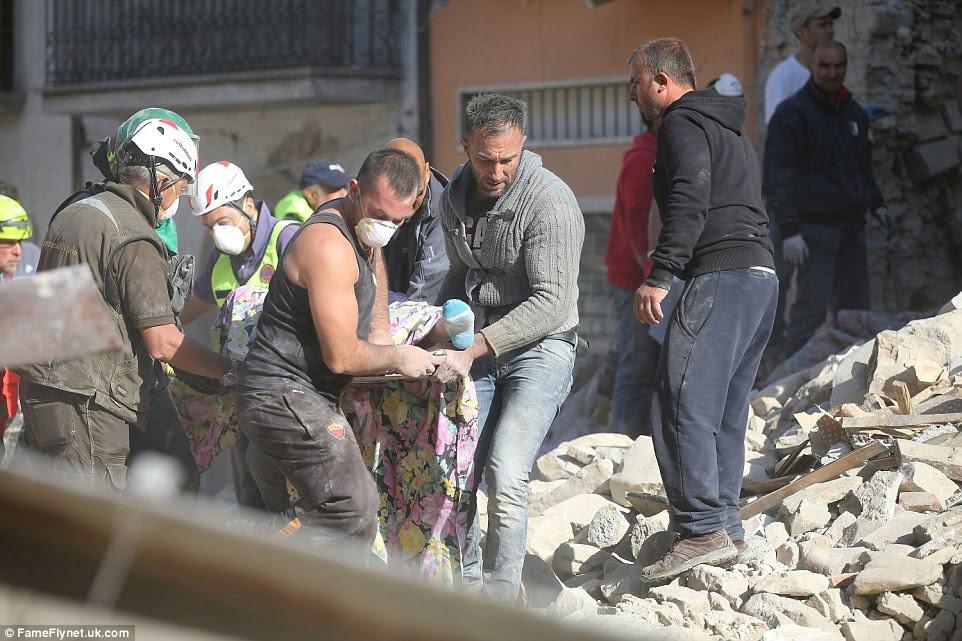 Ajuda: Uma equipe de socorristas e homens locais transportar um corpo em uma maca dos escombros na cidade italiana central da Amatrice