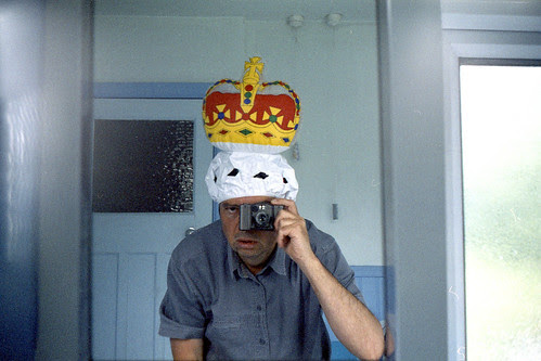 Reflected self-portrait with a Kiev 35A camera and inflatable crown by pho-Tony