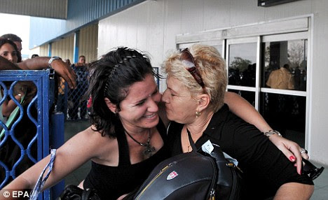 Cuban citizens joyfully greet family members arriving at the Havana airport from the U.S. yesterday - their joy multiplied by the news that Barack Obama has lifted travel restrictions for families