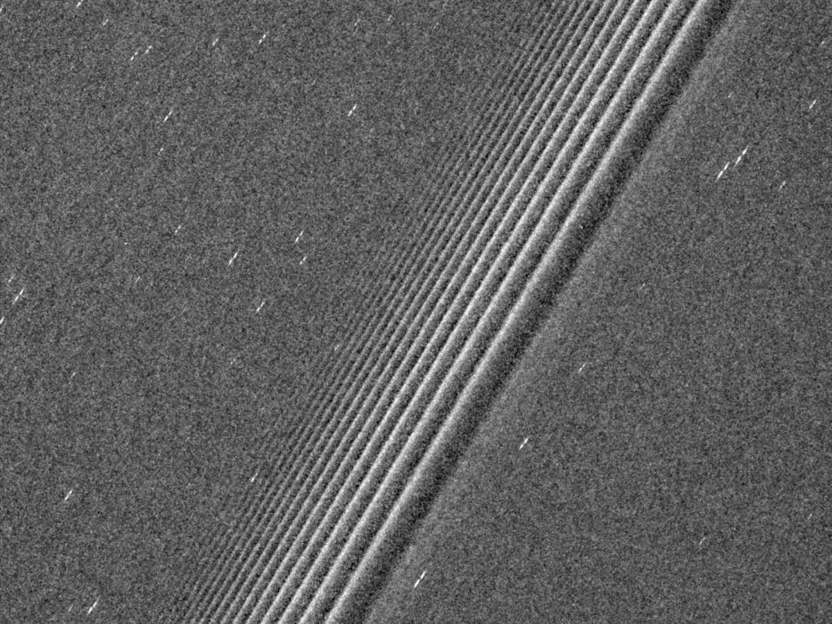 """This grainy image reveals a deep mystery of Saturn: """"propeller objects"""" (the white streaks) that fail to carve out their own lanes in the rings."""