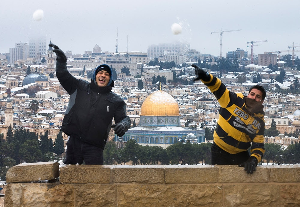 Israeli Arabs throw snowballs as snow covers the Dome of the Rock at the Al-Aqsa mosque in Jerusalem. (Uriel Sinai/Getty Images)