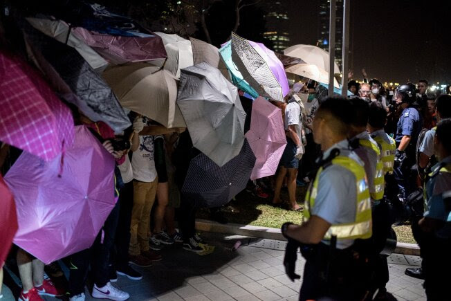 Pro-democracy protesters stand behind umbrellas as police prepare to advance on their positions near the central government offices in Hong Kong on October 15, 2014. Hong Kong has been plunged into the worst political crisis since its 1997 handover as pro-democracy activists take over the streets following China's refusal to grant citizens full universal suffrage.  AFP PHOTO / ALEX OGLE        (Photo credit should read Alex Ogle/AFP/Getty Images)