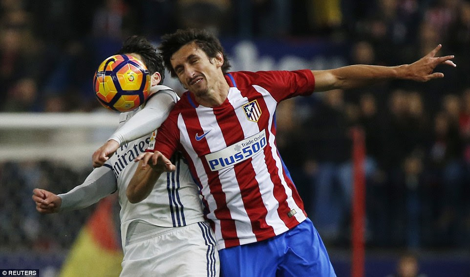 Atletico Madrid defender Stefan Savic contests an aerial duel with Real Madrid midfielder Isco during the first-half