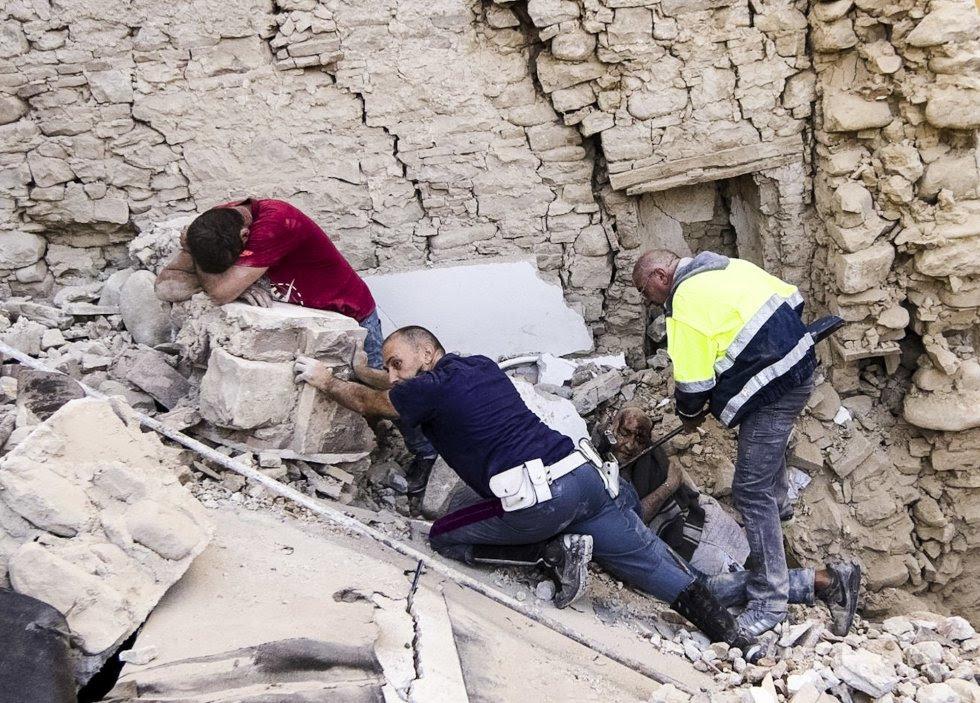 Residentes del pueblo de Amatrice ayudan a las víctimas entre los edificios destruidos.