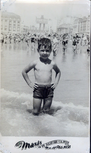 By the sea - One  little boy, dark suit in surf