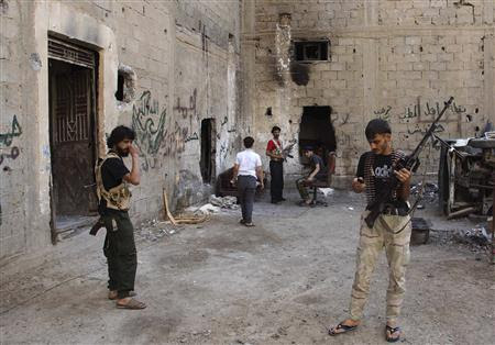 Free Syrian Army fighters carry their weapons as they prepare themselves prior to an offensive against forces loyal to Syria's President Bashar al-Assad in Deir al-Zor July 11, 2013. REUTERS/Khalil Ashawi