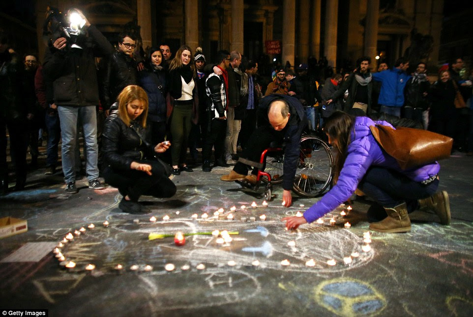 Solidarity: Mourners lay candles at thePlace de la Bourse in Brussels this evening following the terror attacks which have rocked the world