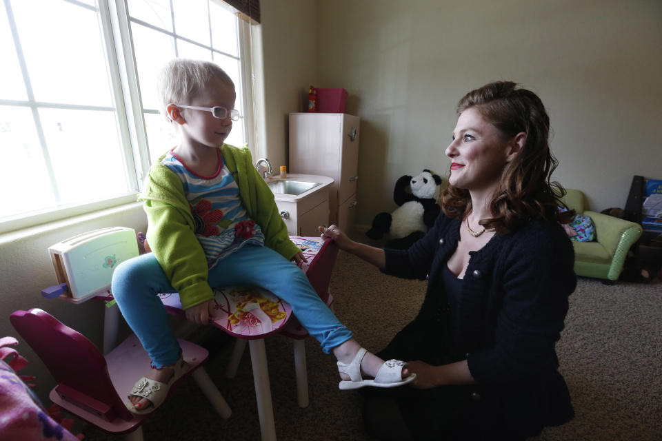 FILE - In this April 29, 2014 file photo, Moriah Barnhart, a mother of a child with severe cancer, sits with her three year old daughter Dahlia, who...