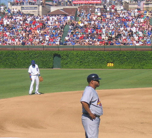 Starlin Castro checking his pantsleg at left, Cards coach Oquendo at right
