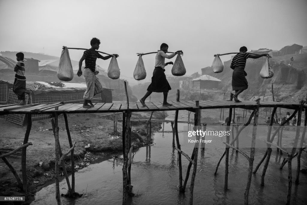 COX'S BAZAR, BANGLADESH - OCTOBER 27: Rohingya Muslim refugee men carry food aid across makeshift bamboo bridges on October 27, 2017 at the Kutupalong refugee camp in Cox's Bazar, Bangladesh. More than 600,000 Rohingya refugees have flooded into Bangladesh to flee an offensive by Myanmar's military that the United Nations has called 'a textbook example of ethnic cleansing'. The refugee population continues to swell further, with thousands more Rohingya Muslims making the perilous journey on foot toward the border, or paying smugglers to take them across by water in wooden boats. Hundreds are known to have died trying to escape, and survivors arrive with horrifying accounts of villages burned, women raped, and scores killed in the 'clearance operations' by Myanmar's army and Buddhist mobs that were sparked by militant attacks on security posts in Rakhine state on August 25, 2017. What the Rohingya refugees flee to is a different kind of suffering in sprawling makeshift camps rife with fears of malnutrition, cholera, and other diseases. Aid organizations are struggling to keep pace with the scale of need and the staggering number of them - an estimated 60 percent - who are children arriving alone. Bangladesh, whose acceptance of the refugees has been praised by humanitarian officials for saving lives, has urged the creation of an internationally-recognized 'safe zone' where refugees can return, though Rohingya Muslims have long been persecuted in predominantly Buddhist Myanmar. World leaders are still debating how to confront the country and its de facto leader, Aung San Suu Kyi, a Nobel Peace Prize laureate who championed democracy, but now appears unable or unwilling to stop the army's brutal crackdown. During a recent visit to Myanmar, U.S Secretary of State Rex Tillerson called for a 'credible' probe into human rights violations against the Rohingya but said he would advise against full sanctions on the country.